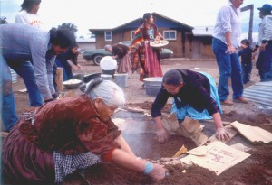 Navajo men and women bake a corn cake in the ground during a Kinaalda ceremony.  The cake is a solar image, alluding to the conception of Changing Woman's twins by Sun.